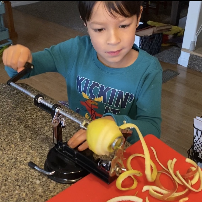 boy using an apple peeler corer slicer