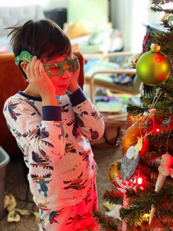 boy looking at christmas tree through 3d glasses