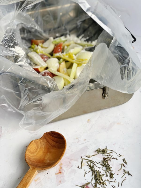 roasting pan with onions and apples in oven roasting bag