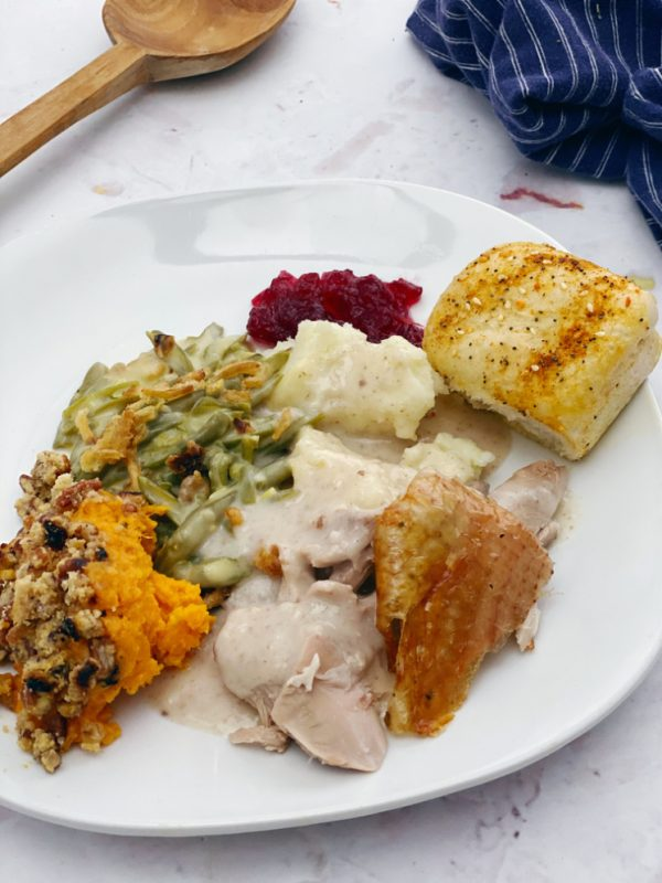 Plate of thanksgiving dinner with turkey sweet potatoes green beans cranberries mashed potatoes and a roll